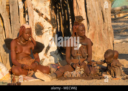 Himba people, Namibia- people siting near the huts in the village - Stock Photo