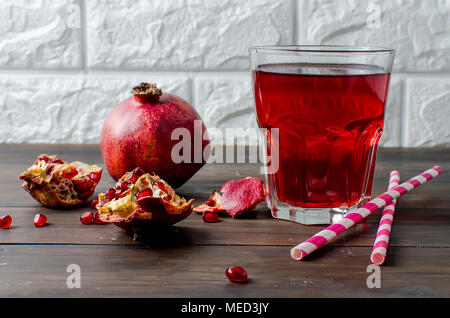 Fresh pomegranate juice in a glass with fruit pomegranates on a dark old wooden background - Stock Photo