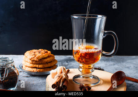Pouring  tea in cup on dark  background, Cup of tea, biscuits, spices for tea. - Stock Photo