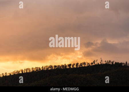 A silhouette of a mountain peak at sunset, beneath sun rays coming out through some clouds - Stock Photo