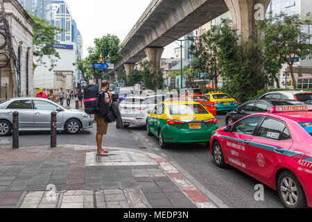 A backpacker waits for an empty taxi in heavy traffic on Sukhumvit Road, Bangkok, Thailand - Stock Photo