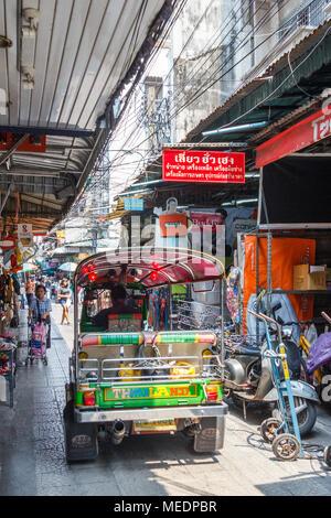 A tuk tuk makes its way along the narrow Sampeng Lane, Chinatown, Bangkok, Thailand. - Stock Photo