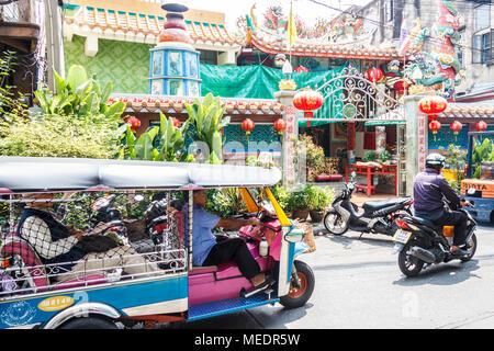 Tuk tuk with passenger negotiating its way through the back streets of Chinatown, Bangkok, Thailand - Stock Photo