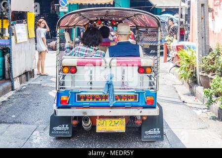 Tuk tuk with passengers negotiating its way through the back streets of Chinatown, Bangkok, Thailand - Stock Photo