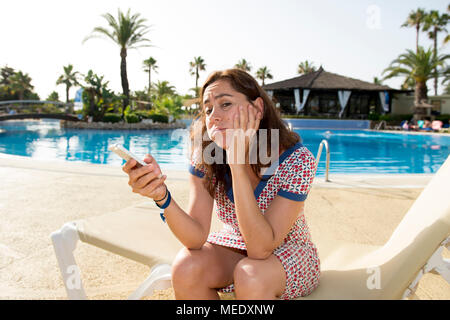 Pretty attractive latin woman unhappy and stressed on her smart phone by the pool on holidays at a resort - Stock Photo