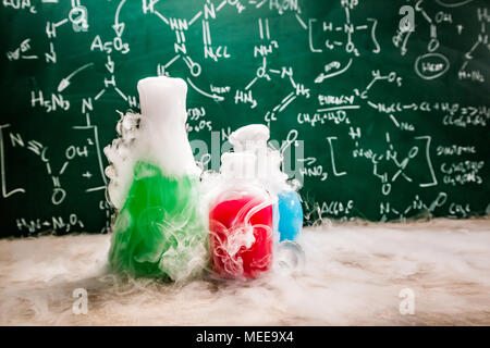 Dynamic reaction in school laboratory with color beakers - Stock Photo