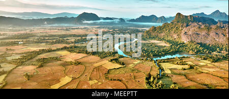 Aerial bird's-eye sunrise time view on valley landscape with karst mountains, river and rice fields. Laos, Vang Vieng. - Stock Photo