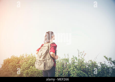 Man Traveler climbing on mountain summit over clouds Travel Lifestyle success concept adventure active vacations outdoor extreme sport - Stock Photo