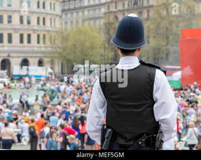 Rear view of Police Officer Watching Over Crowds in Trafalgar Square, London - Stock Photo