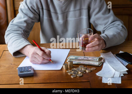Close up man with calculator counting, making notes at home, hand is writes in a notebook. Stacked coins arranged at deesk. Savings finances concept. - Stock Photo