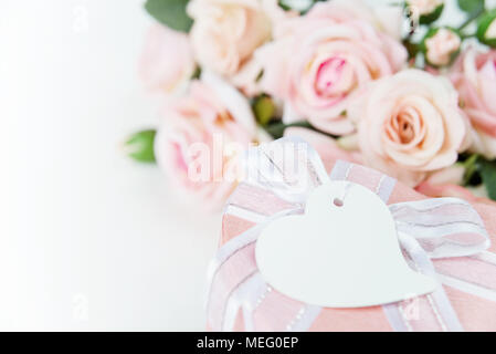 Gift box with label, ribbon and pink rose flowers on a light background - Stock Photo