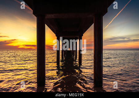 Dramatic sunset view from under Brighton Jetty, South Australia - Stock Photo