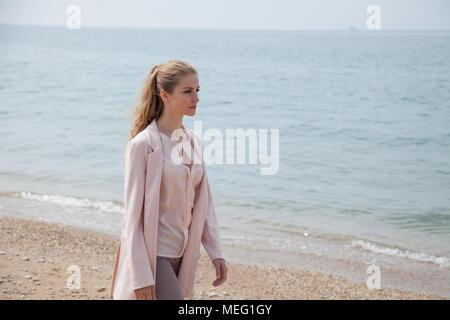 blonde girl walks along the beach of the sea coast - Stock Photo