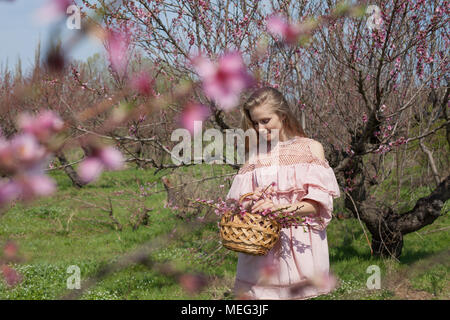 blonde girl in pink dress is collecting flowers in the garden - Stock Photo