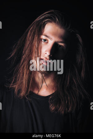 Close-up portrait of a handsome long-haired young man - Stock Photo