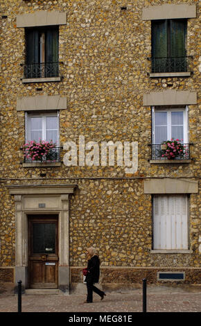Local walking past a town home on the outskirts of Paris. - Stock Photo