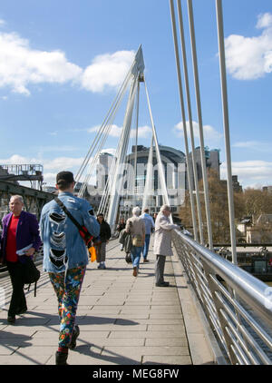 LONDON, ENGLAND - APRIL 17th 2018: Tourists walking on the Golden Jubilee Bridge in London. - Stock Photo