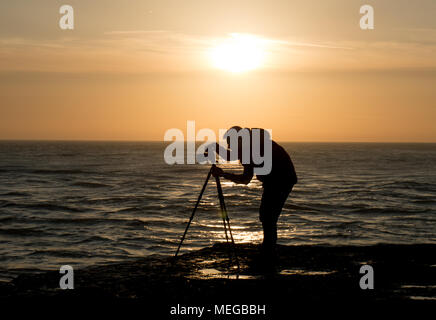 A photographer composes his shot carefully at sunset near the sea - Stock Photo