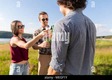 Group of friends at BBQ party toasting with drinks  - Stock Photo