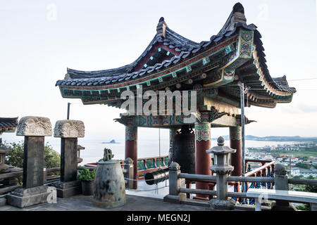 Temple bell house with view over coastline at Sanbanggulsa temple during sunset, Sanbang-ro, Jeju Island, South Korea - Stock Photo