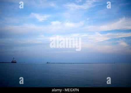 Minimalist blue toned water landscape on Lake Michigan with a distant pier and navigation beacon on the horizon and vignette - Stock Photo