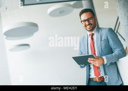 Portrait of young businessman with digital tablet in office - Stock Photo