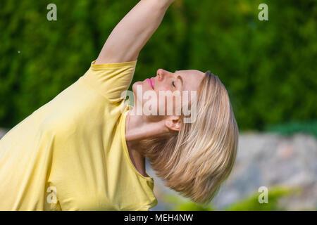 Beautiful pregnant woman doing prenatal yoga on nature. - Stock Photo