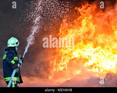 Firefighter battling with fire, fire rescue looking for survivor. Huge flames burned a recycling company in Tirana, fireman extinguishing the blaze