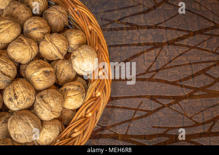 Walnuts in a wooden bowl on a wooden table walnuts with shells - Stock Photo
