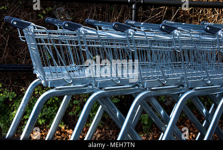 A line of shopping trolleys parked outside a supermarket - Stock Photo
