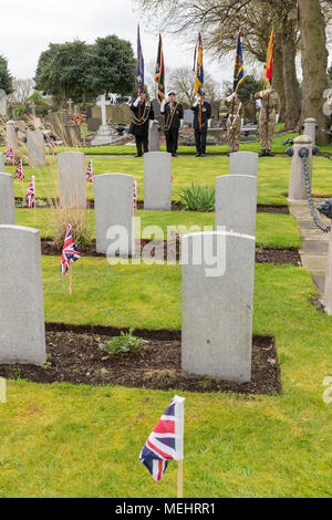 Standard Bearers proudly hold their colours near to the graves of ex-servicemen at Soldiers' Corner during the Service to commemorate the anniversary of ANZAC Day - Warrington, UK, 22 April 2018. The Anniversary of ANZAC Day has been commemorated on Sunday 22 April 2018 within Soldiers' Corner of Warrington Cemetery when the Deputy Mayor, Cllr Karen Mundry, Cadets from the Queen's Lancashire Regiment, Warrington Sea Cadets and many veterans were in attendance Credit: John Hopkins/Alamy Live News - Stock Photo