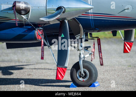 21 April 2018, Germany, Norderney: A roll-away lock and different safety devices are fixed to a parked small propeller aircraft at the airfield. Photo: Lino Mirgeler/dpa - Stock Photo