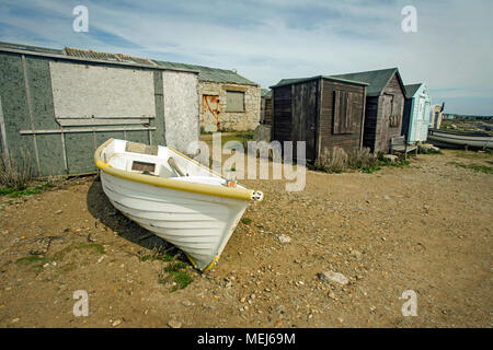 A white rowing boat on the shore by ramshackle wooden huts used by fishing personnel. - Stock Photo