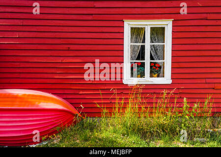 Norwegian wooden house in Solvorn, Norway, red facade of a typical cottage with small boat on the exterior wall - Stock Photo