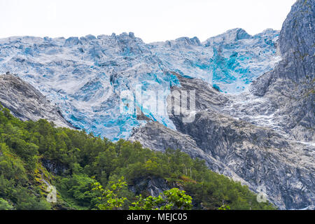 glacier Supphellebreen, part of the Jostedalsbreen National Park, Norway, near Fjaerland, blue shimmering glacial ice in a rough mountain landscape - Stock Photo