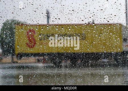 Raindrops on the outside of a car window with a yellow road haulage lorry in the background during a rainstorm in Dausa, Rajasthan, north India - Stock Photo