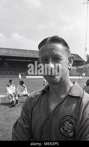 1964, historical picture, the head coach of Charlton Athletic FC at their football ground, the Valley, with players behind him on the pitch. His top has a large badge stating he is an official coach of the English Football Association (FA) - Stock Photo