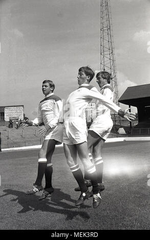 1964, Charlton Athletic FC, historical picture showing three Charlton football players including Billy Bonds on the pitch at the Valley, their  ground, leaping up showing off their new football kit. Between 1964 and 1966 the Charlton players wore a smart all white kit with red shoulders and the hand and sowrd badge first appeared on the shirt. - Stock Photo