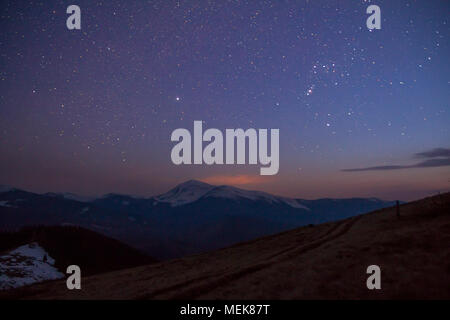 Majestic view of fantastic starry dark sky over magnificent Carpathian mountains covered with evergreen forest and snow-capped peaks in distance. Brea - Stock Photo