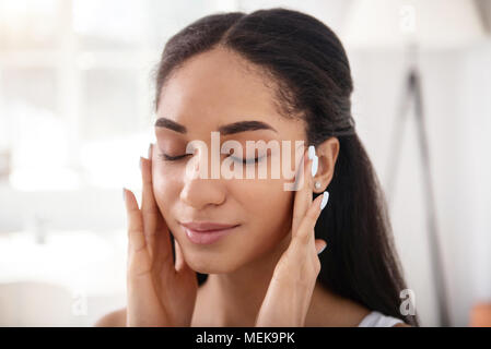 Close up of young woman doing face-lifting massage - Stock Photo