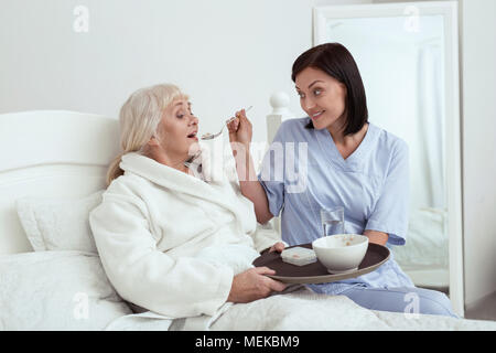 Happy caregiver feeding elder woman - Stock Photo