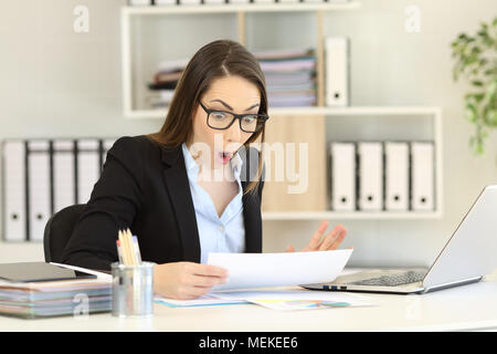 Amazed office worker reading sales report sitting in a desktop at workplace