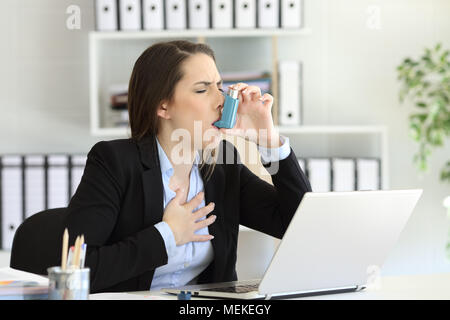 Asmathic executive having an asthma attack inhaling with a inhaler at office - Stock Photo
