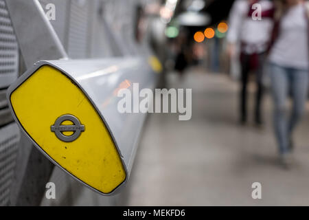 In foreground, end of handrail at Westminster underground station, London showing TFL roundel. In background blurred commuters walking along platform, - Stock Photo