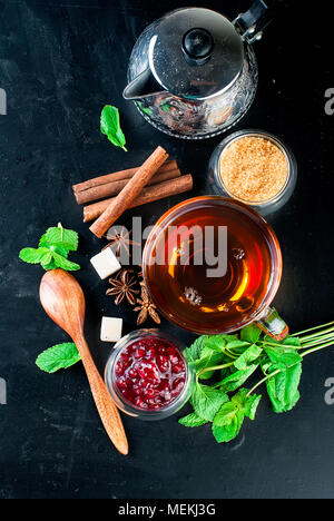 autumn warming tea with lemon, mint in a glass cup and raspberry jam on a black background. copy space, - Stock Photo