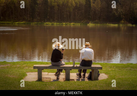 Old couple sat on bench in front of lake enjoying a flask of tea or coffee in sunshine - Stock Photo