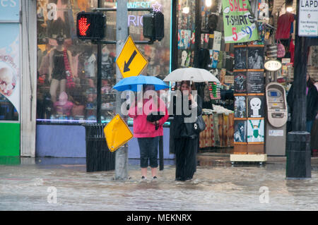 HOLLYWOOD - January 21, 2018: Unidentified women trying to cross the street on heavy rainy day in the city of Hollywood, CA. - Stock Photo