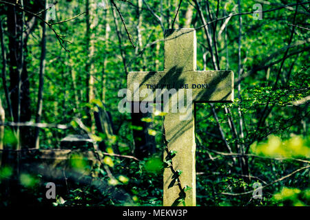 A cross saying 'Thy Will Be Done' at Abney Park cemetery, one of the Magnificent Seven cemeteries in London, UK - Stock Photo
