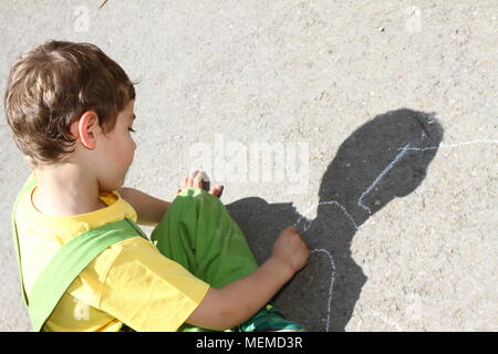 Cute boy write with colored chalks on a kids playground. Little kid draws with chalks. Vacation concept. Education concept. School and fun time. Play - Stock Photo
