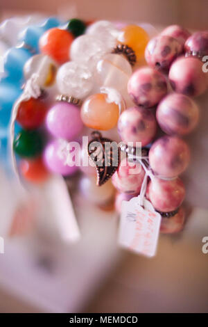 Colorful bracelets are handmade on a light background - Stock Photo